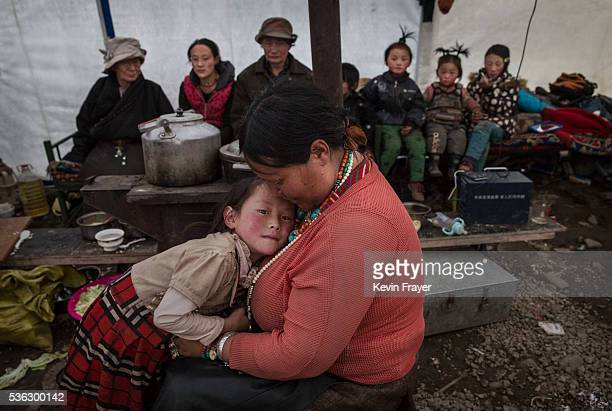 Tibetan family gather in their tent after a day of working in the mountains at a temporary camp for cordycep pickers on May 23 2016 on the Tibetan...