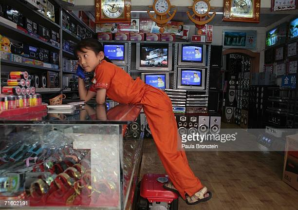 Tibetan girl talks on the phone at her father's shop on August 6 2006 in Lhasa of Tibet Autonomous Region China Lhasa's face is ever changing as it...
