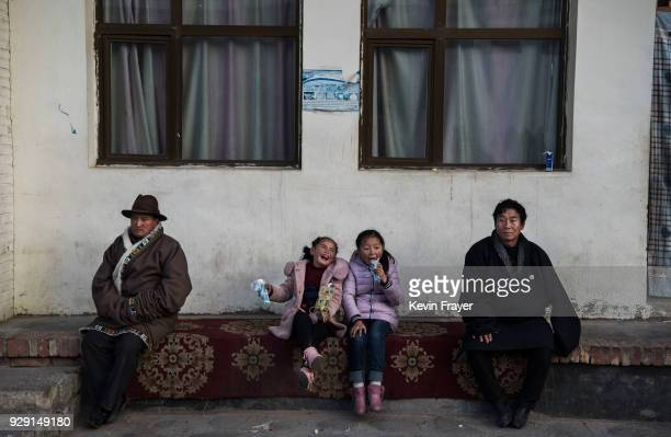 Tibetan girls joke as they eat ice cream at the Rongwo Monastery during Monlam or the Great Prayer on March 1 2018 in Tongren also known as Rebkong...