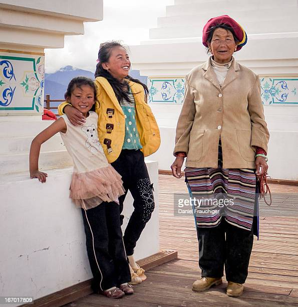 Tibetan grandmother with two grandchildren visiting Buddhist pagodas on July 28 2011 in Deqin China