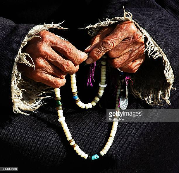 Tibetan herder holds a beads as she watches guests visiting her village in the district of Naqu July 7 2006 in Lhasa Tibetan Autonomous Region China...
