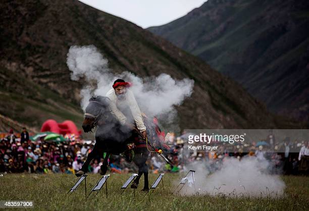 Tibetan horseman shoots a target as he performs during a riding skills competition at a local government sponsored festival on July 26 2015 on the...