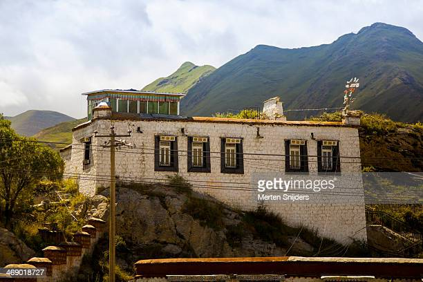 tibetan house built against a hill - merten snijders stock-fotos und bilder