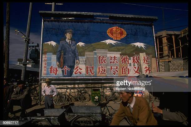 Tibetan locals framed by Chinese billboard proclaiming by law it is the duty of every citizen to pay taxes, re intrusive Chinese presence.