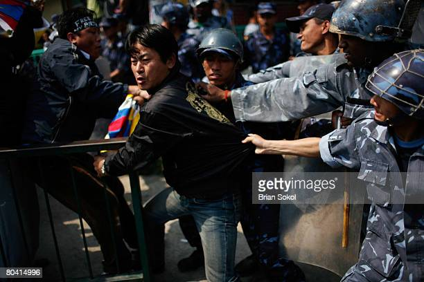 Tibetan man attempts to hold onto a railing and a Tibetan flag as he is forcibly detained by Nepali police during a proTibet peace protest near the...