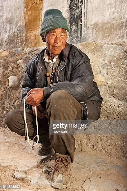 Tibetan man praying with rosary, near Lo Manthang