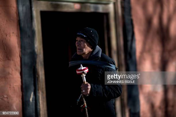 A Tibetan man swings a prayer wheel outside the Labrang Temple during Tibetan New Year celebrations in Labrang on the QinghaiTibet Plateau on...