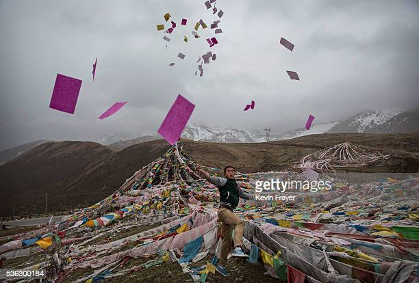 Tibetan man throws prayers in the air at a high altitude pass on May 22 2016 on the Tibetan Plateau near Yushu town in the Yushu Tibetan Autonomous...