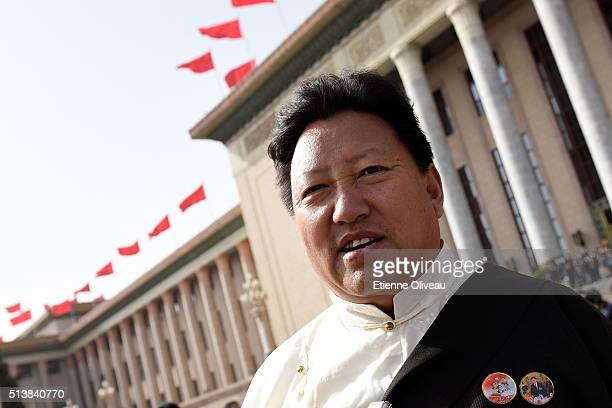 Tibetan minority delegate stands in front of the Great Hall of the People during the opening session of the China's National People's Congress on...