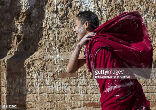 Tibetan monk enjoying a water fight after the yearly renovation of the Rongwo monastery Tongren County Longwu China on October 27 2017 in Longwu China