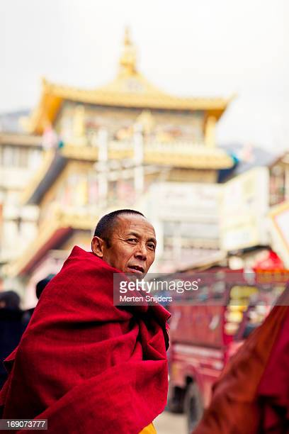 tibetan monk in front of temple - merten snijders stock-fotos und bilder