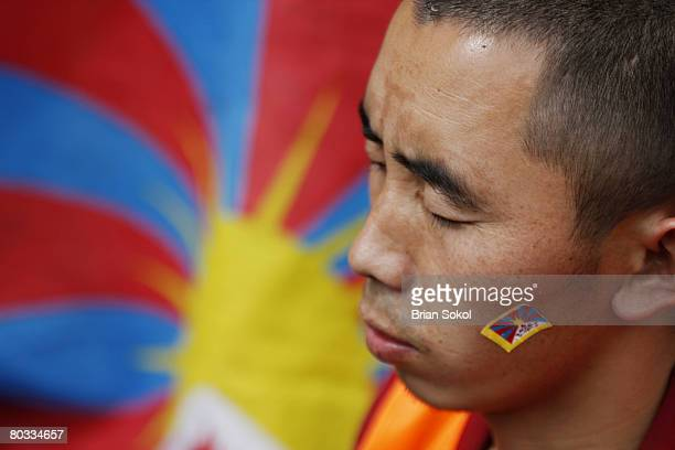 Tibetan monk meditates in front of a Tibetan flag shortly before being detained by Nepali police during aTibetan peace rally in front of the United...