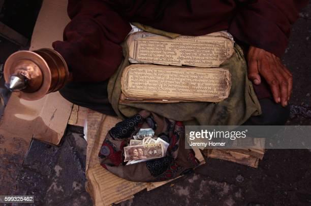 Tibetan Monk Praying with Prayer Book and Wheel