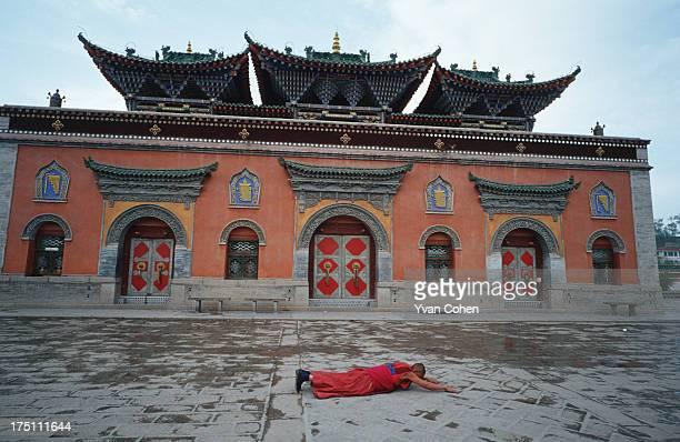 Tibetan monk prostrates in front of the entrance to the Kumbum monastery the birthplace of Je Tsongkhapa the founder of the Gelugpa Sect of Tibetan...