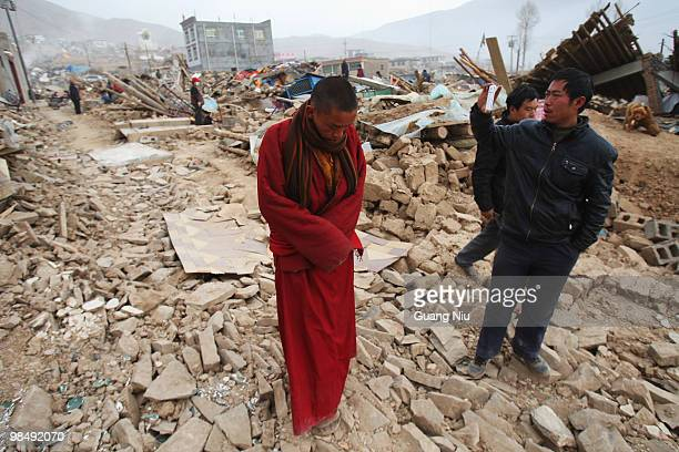Tibetan monk walks down a street surrounded by collapsed buildings following a strong earthquake, on April 16, 2010 in Jiegu, near Golmud, China. It...