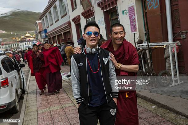 Tibetan monk walks with a friend during a break from harvesting cordycep fungus on the 15th day of Saka Dawa the holiest day of the Buddhist calendar...