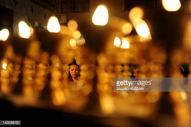 Tibetan monks offer prayers at their refugee colony of Majnu Ka Tilla in New Delhi on March 29 for Tibetan exile Janphel Yeshi who set himself on...