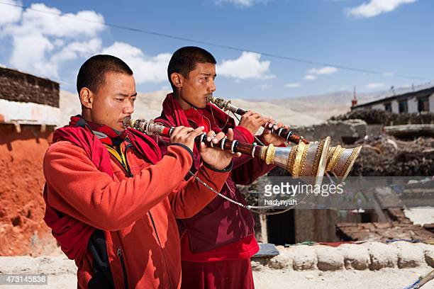 Tibetan monks playing buddhist horns in Upper Mustang