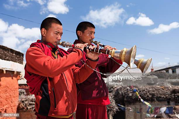 tibetan monks playing buddhist horns - red tube top stock photos and pictures