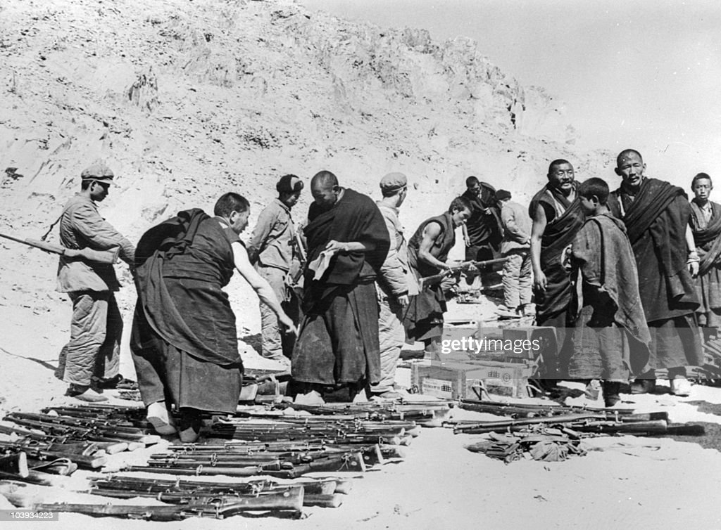 Tibetan monks, surrounded by soldiers of the Chinese Popular Liberation Army, lay down arms in April 1959 somewhere in the Tibetan mountains after an unsuccessful armed uprising against Chinese rule. As a result, the Dalai Lama, the head of Tibet's Buddhist clergy and thus the region's spiritual leader, fled with some 100,000 supporters to northern India, where a government-in-exile was established. The Chinese ended the the former dominance of the lamas (Buddhist monks) and destroyed many monasteries. Tibet (Xizang), occupied in 1950 by Chinese Communist forces, became an 'Autonomous Region' of China in September 1965, but the majority of Tibetans have continued to regard the Dalai Lama as their 'god-king' and to resent the Chinese presence, leading to intermittent unrest.