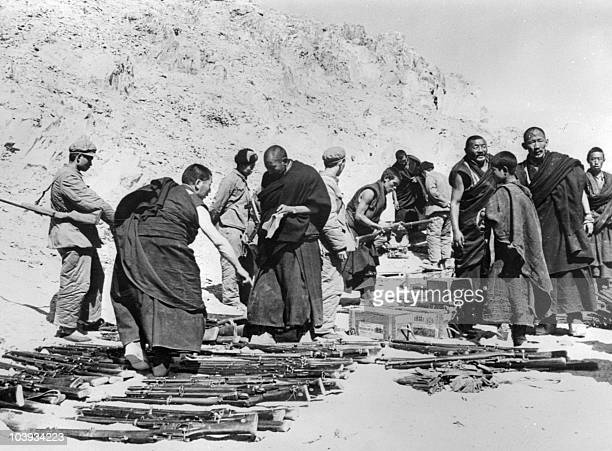 Tibetan monks surrounded by soldiers of the Chinese Popular Liberation Army lay down arms in April 1959 somewhere in the Tibetan mountains after an...