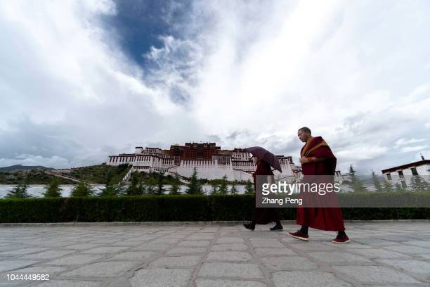Tibetan monks walk in front of the Potala Palace. The Potala Palace in Lhasa, the largest and most complete ancient palace complex in Tibet, is now a...