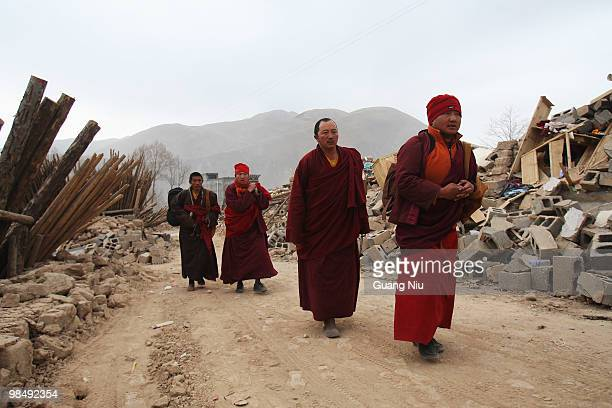 Tibetan monks walk up a street surrounded by collapsed buildings following a strong earthquake, on April 16, 2010 in Jiegu, near Golmud, China. It is...