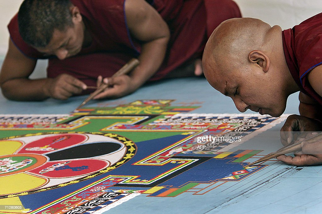 Tibetan monks work on a mandala, part of : News Photo