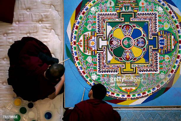 Tibetan monks work on creating an intricate sand drawing known as a mandala at the Broward County Main Library February 6 2007 in Fort Lauderdale...