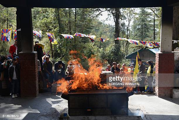 Tibetan mourners look on as the body of Dorje Tsering is cremated in the Indian town of McLeod Ganj on March 6 2016 Hundreds of grieving Tibetans on...