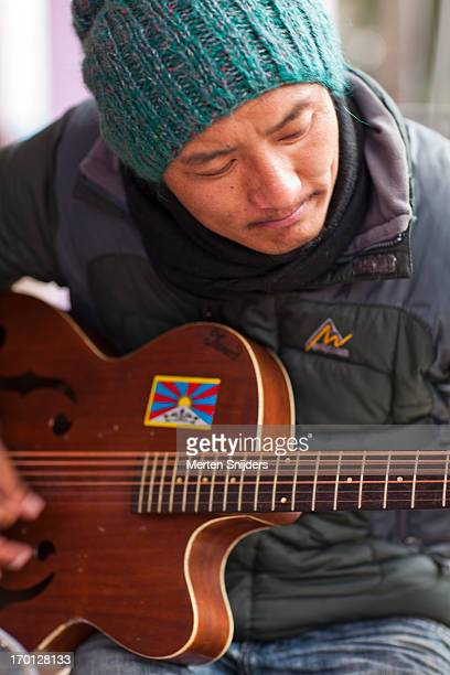 tibetan musician playing guitar - merten snijders stock pictures, royalty-free photos & images