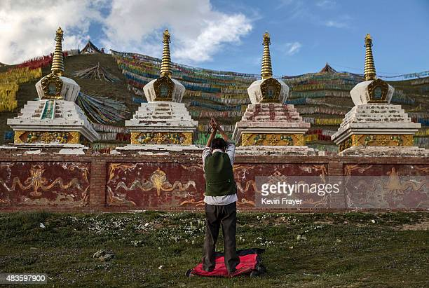 Tibetan nomad prays in front of Buddhist chortans on July 23 2015 on the Tibetan Plateau in Madou County Qinghai China Tibetan nomads face many...