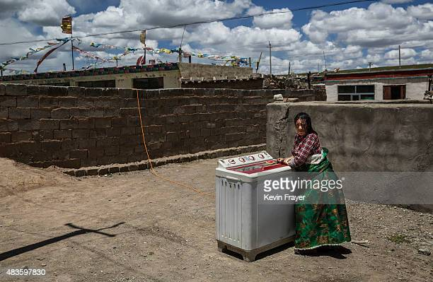 Tibetan nomad stnads in front of her washing machine outside her home in a government resettlement community on July 23 2015 on the Tibetan Plateau...