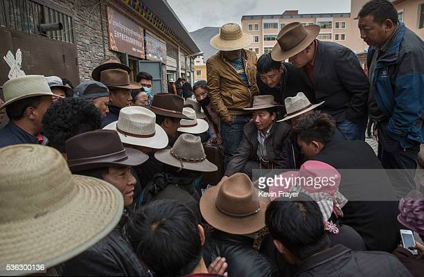 Tibetan nomads crowd around as they bid on cordycep fungus for sale at a market on May 22 2016 on the Tibetan Plateau in Yushu town in the Yushu...