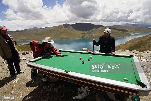 Tibetan nomads play snooker beside the Yamdrok Lake on August 31 2006 in Langkazi County of Tibet Autonomous Region China Chinese tourists are...