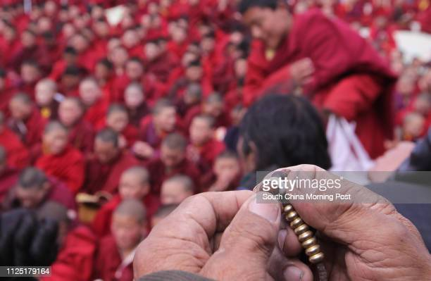 Tibetan old man holds Buddhism beads whole Tibetan monks and nuns chant Buddhism surtas at a special memorial service on the hillside in Zhaxi Datong...