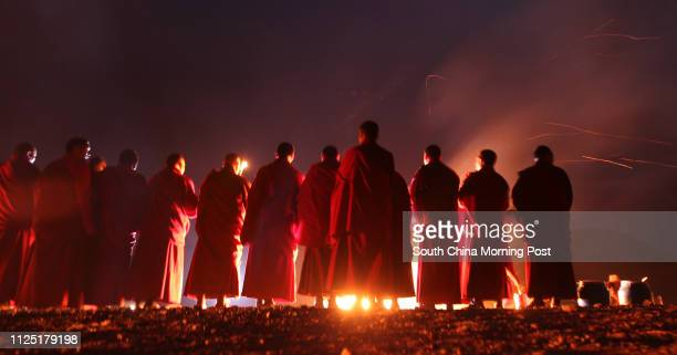 Tibetan people and monks lighten up butter oil lamps on the hillside in Zhaxi Datong Village where the mass cremation was held last year for the...