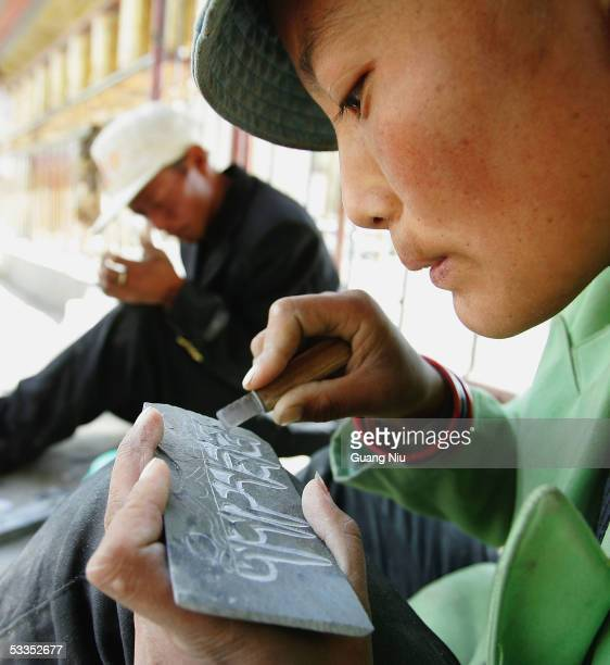 Tibetan people carve Buddhism scriptures onto stone to sell outside the Pelkor Chode Monastery on August 6 2005 in Gyantse of Tibet China Tibet has...