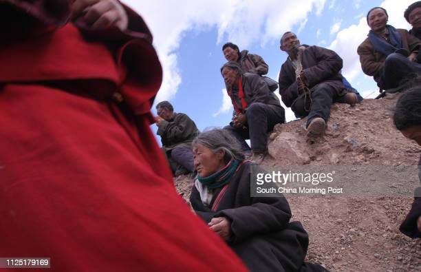 Tibetan people chant Buddhism sutras at a special memorial service on the hillside in Zhaxi Datong Village where the mass cremation was held last...