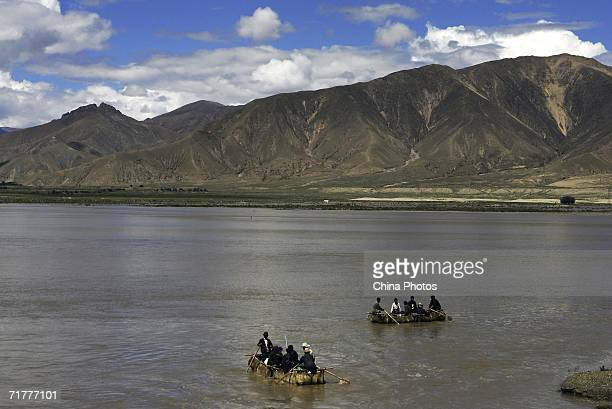 Tibetan people row cowskin rafts on the Brahmaputra River on August 30 2006 in Renbu County of Tibet Autonomous Region China Cowskin is a traditional...