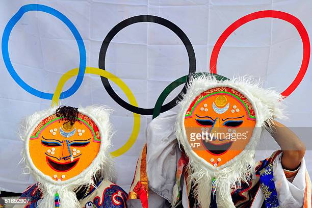 Tibetan performers dressed in traditional costumes wait in front of an Olympic logo prior to the 2008 Beijing Olympic Games torch relay ceremony in...