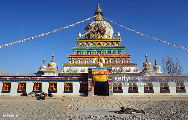 A Tibetan pilgrim prostrates herself in prayer while cirling the fivetiered stupa at Gomar Gompa in Repkong during ongoing celebrations for Monlam or...