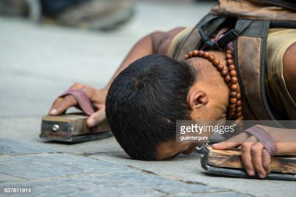 Tibetan pilgrim prostrating at the Barkhor in Lhasa, Tibet.