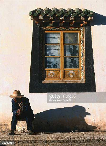 Tibetan pilgrim takes short break outside Songzanlin Monastery, Zhongdian, China