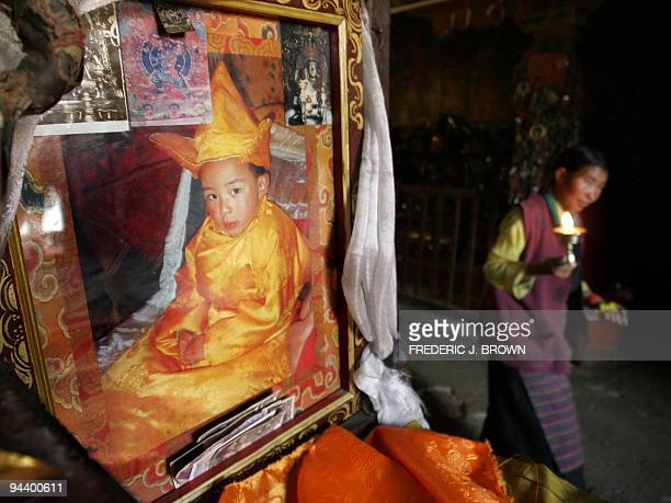 A Tibetan pilgrim walks with her butter lamp past a portrait of Beijing's Communist governmentappointed candidate for the 11th Panchen Lama a boy...