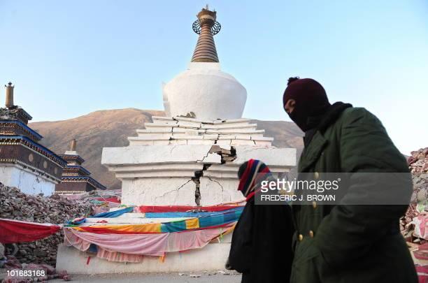 Tibetan pilgrims walk past a quake damaged stupa while circumambulating around the City of Mani Stone in Xinzhai Village just outside of Jiegu Yushu...