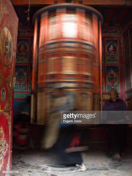 Tibetan pilgrims walking around big prayer wheel in Labrang Monastery in Xiahe town, Gansu, China