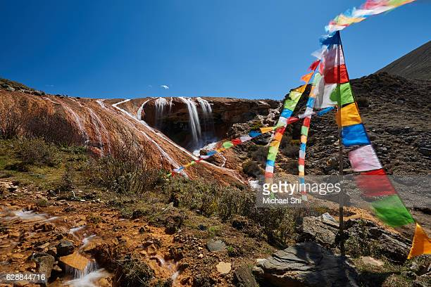 Tibetan pray flags are flying in strong wind near a small waterfall,  the source of branches of many Asian big rivers,  to show reverence to water at high altitude in Garze, Sichuan, China.