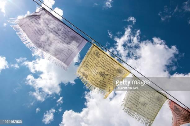 tibetan prayer flags against a blue partly cloudy sky - laurent sauvel photos et images de collection