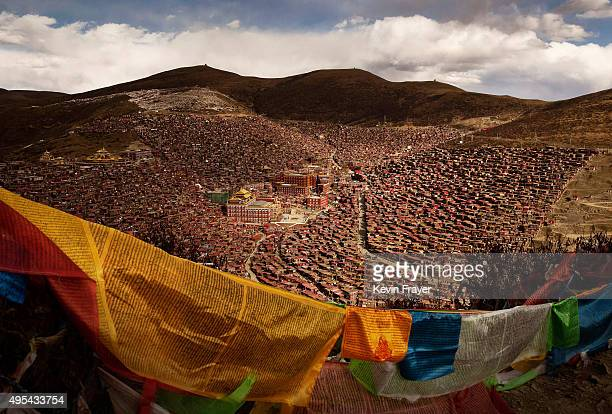Tibetan prayer flags, known as Lung-ta, flutter on a hillside above the Larung Wuming Buddhist Institute on October 30, 2015 in the Larung Valley of...